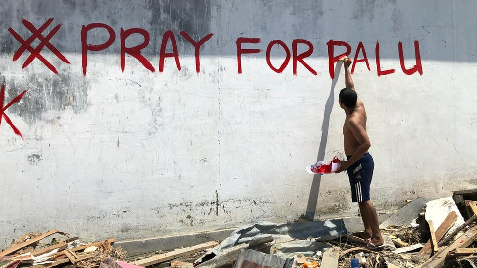 A man paints the words Pray for Palu on a wall in Palu