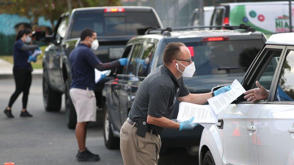 Personas con mascarillas entregando aplicaciones para la solicitud de desempleo a automovilistas en Hialeah, Florida.