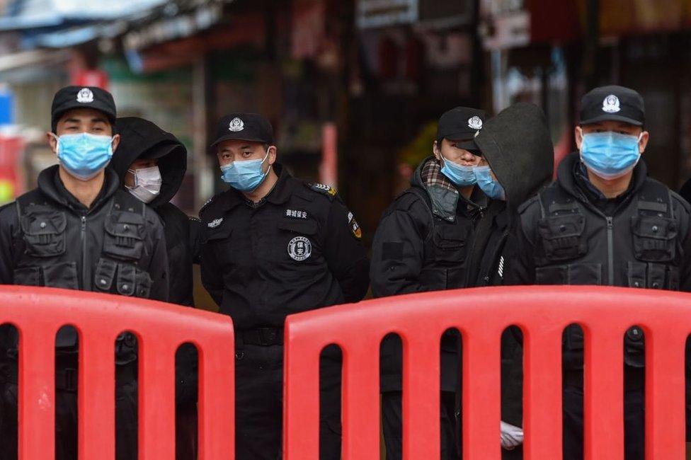 Policías vigilan el mercado de marisco de Huanan, en Wuhan, China.