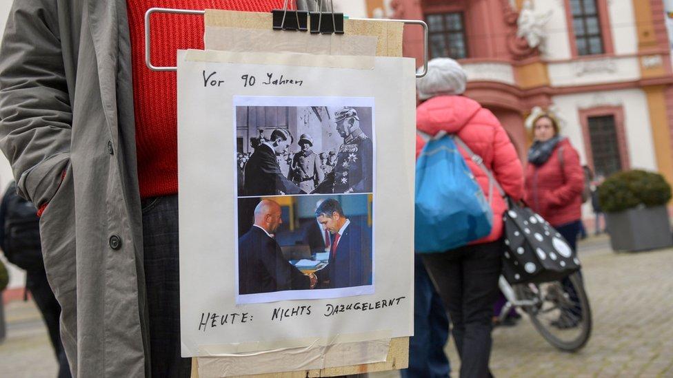 Un manifestante en Alemania porta un cartel comparando lo sucedido en Turingia con el ascenso de Adolf Hitler.