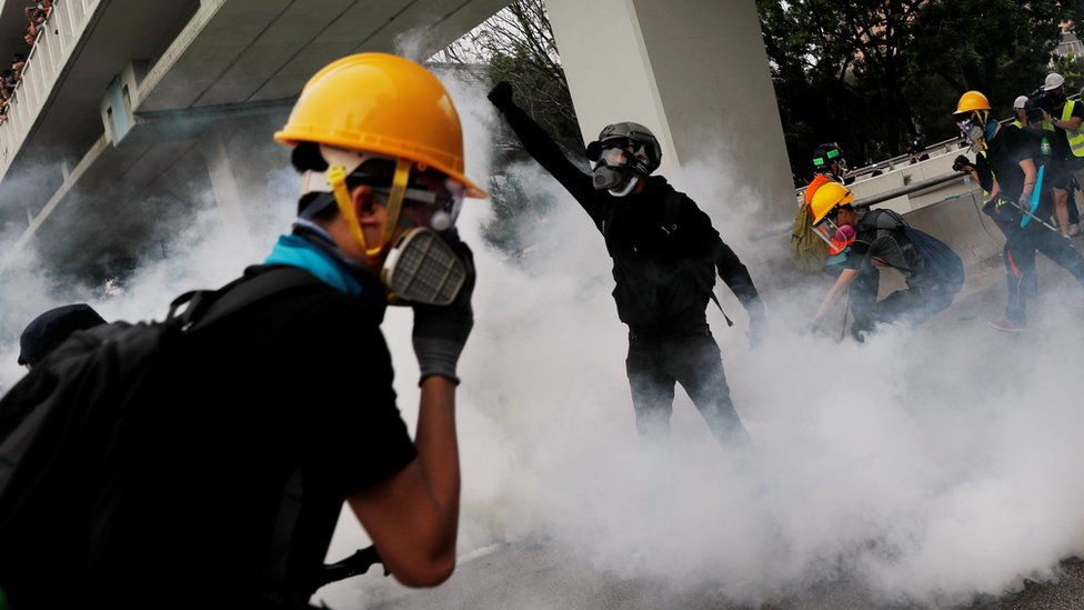Demonstrators react to a tear gas during a protest against the Yuen Long attacks in Yuen Long, New Territories, Hong Kong, China July 27, 2019.