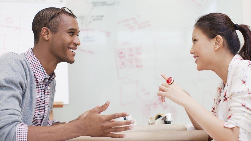 Un hombre y una mujer sonrientes cara a cara en una oficina