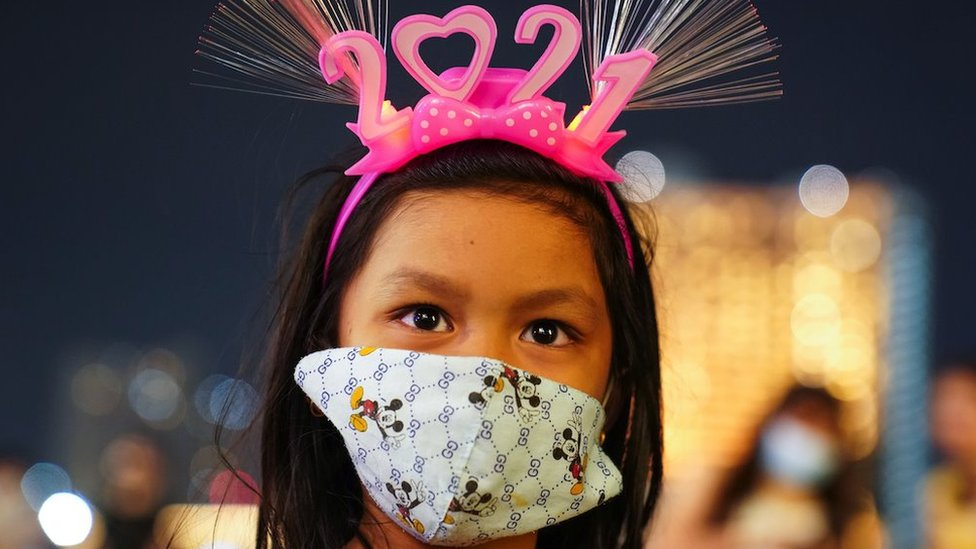 """Uma jovem usando uma máscara protetora e uma faixa na cabeça """"2021"""" observa um shopping center durante as celebrações da contagem regressiva do Ano Novo em Bangcoc"""