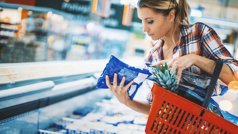 Žena gleda kesu smrznute hrane
