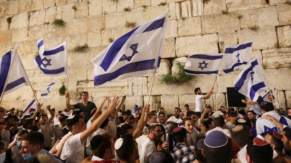 يهود يرقصون بالأعلام الإسرائيلية بالقرب من الحائط الغربي، أقدس أماكن الصلاة اليهودية في البلدة القديمة بالقدس. الصورة: 9 مايو 2021