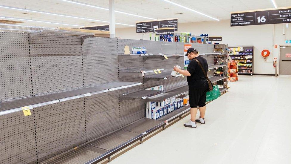 Un hombre frente a un estante vacío.
