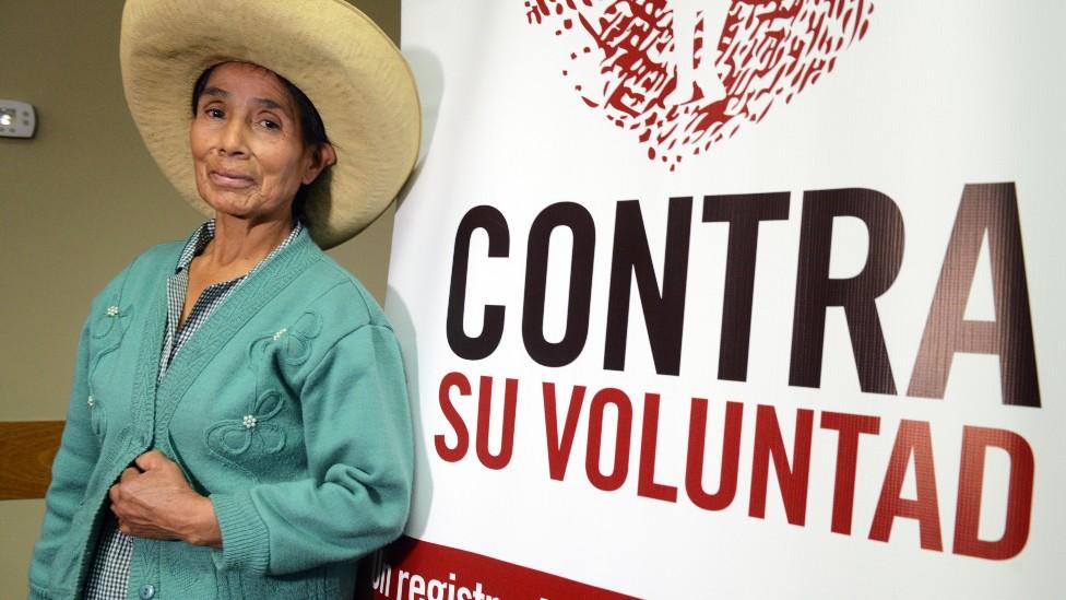 """Esperanza Huayama junto a un cartel que dice """"contra su voluntad"""""""