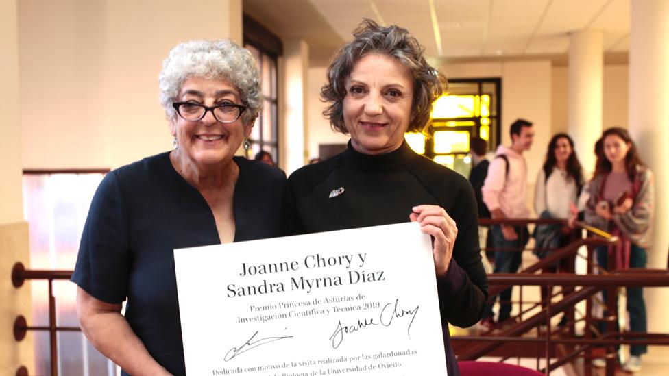 Joanne Chory y Sandra Díaz con un cartel donde se lee que fueron galardonadas con el Premio Princesa de Asturias