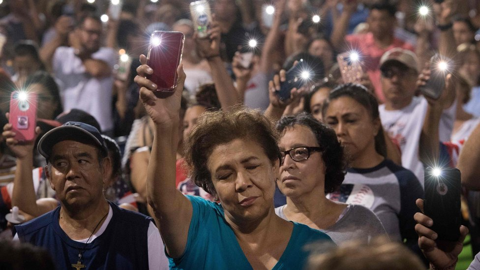 People hold up their phones during a prayer and candle vigil organized by the city, after a shooting left 20 people dead at the Cielo Vista Mall Wal-Mart in El Paso, Texas, on August 4, 2019.
