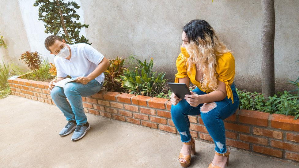 Dos personas con mascarilla guardando la distancia social.