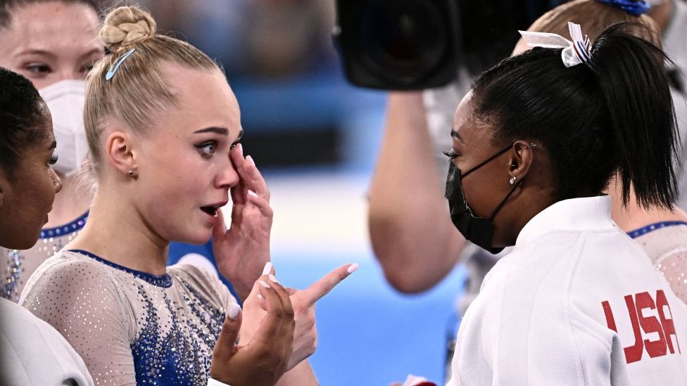 Russia's Angelina Melnikova (L) is congratulated by USA's Simone Biles as Russia wins the artistic gymnastics women's team final during the Tokyo 2020 Olympic Games