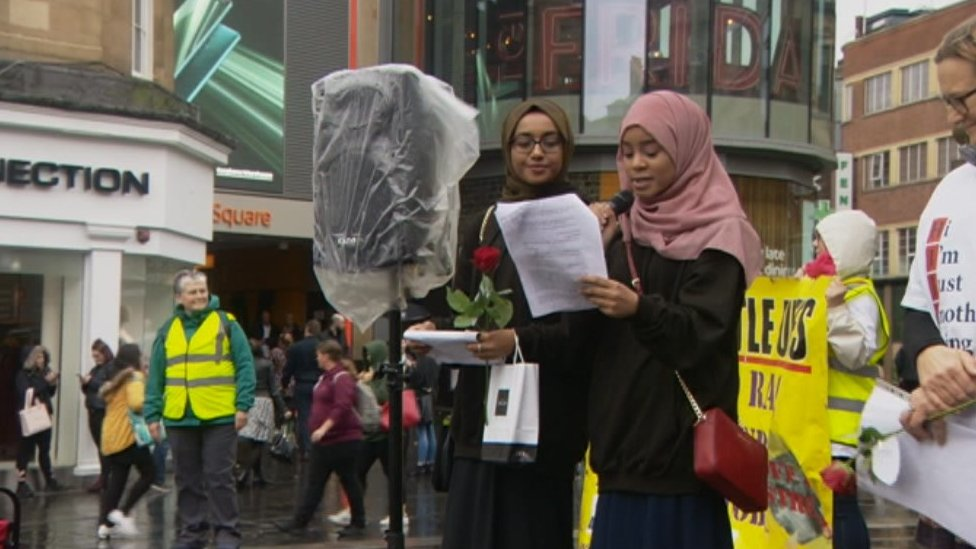 A Muslim woman speaks to the crowd outlining her experiences of abuse on public transport