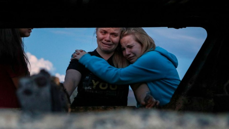 Miembros de la familia LeBarón lloran mientras miran el auto quemado donde al menos nueve personas fueron asesinados y quemados durante una emboscada de hombres armados en Bavispe, Sonora, el 5 de noviembre de 2019.