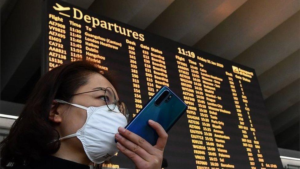 Una mujer con un teléfono frente a un tablero de aeropuerto