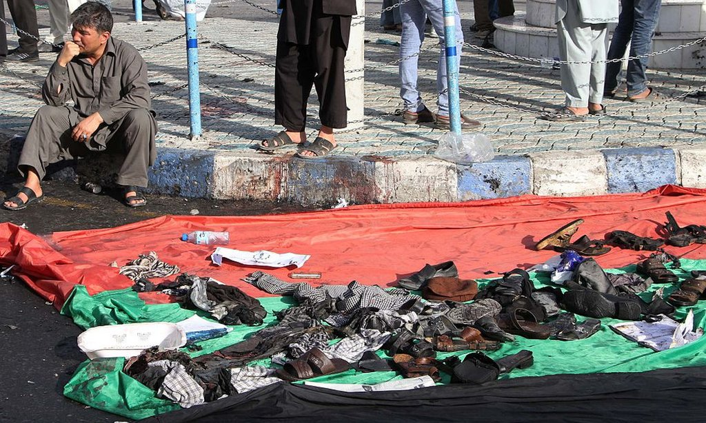 A man sits next to a blanket holding the possessions of people caught in a 2016 Kabul bombing