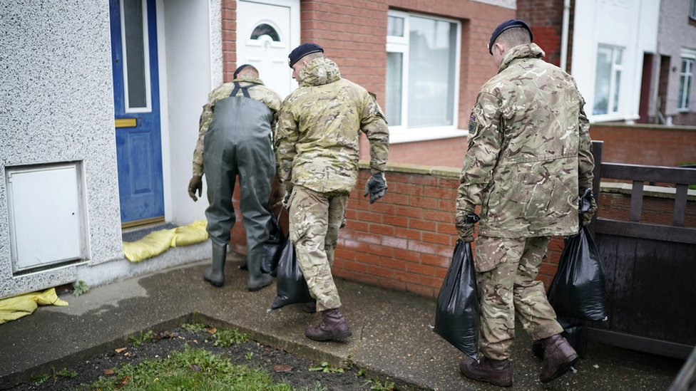 Three soldiers carrying sandbags to a house