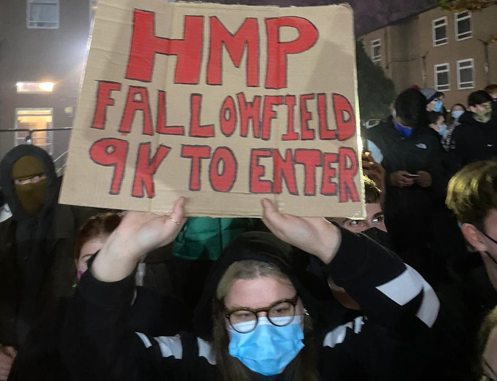 "A student holds a sign reading ""HMP Fallowfield, 9k to enter"""