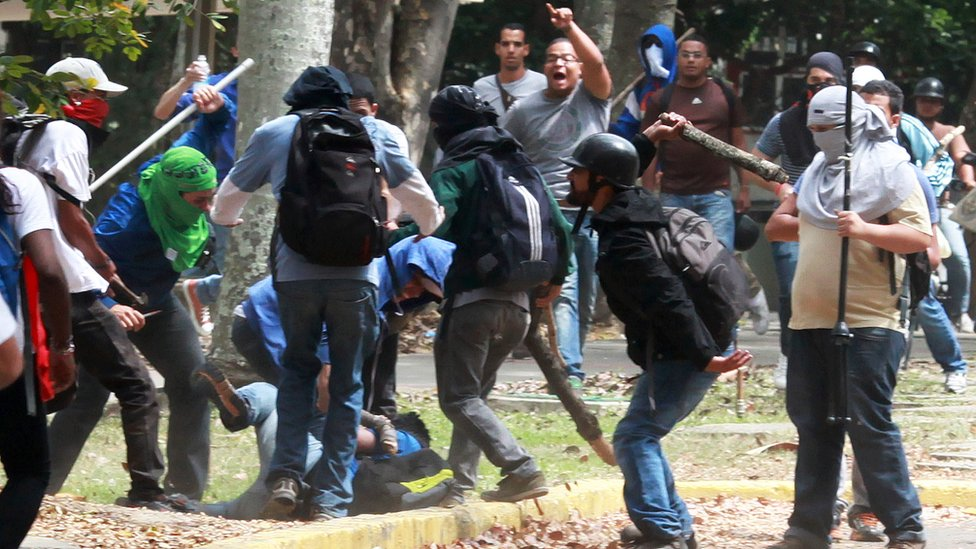 Members of a 'colectivo' pro government group beat an opposition student who was taking part in a protest in Caracas on 3 April 2014