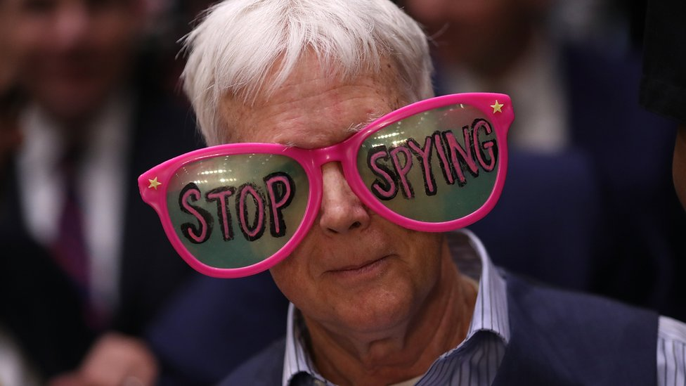 """a protester in a pair of oversized glasses emblazoned with the words """"stop spying"""""""