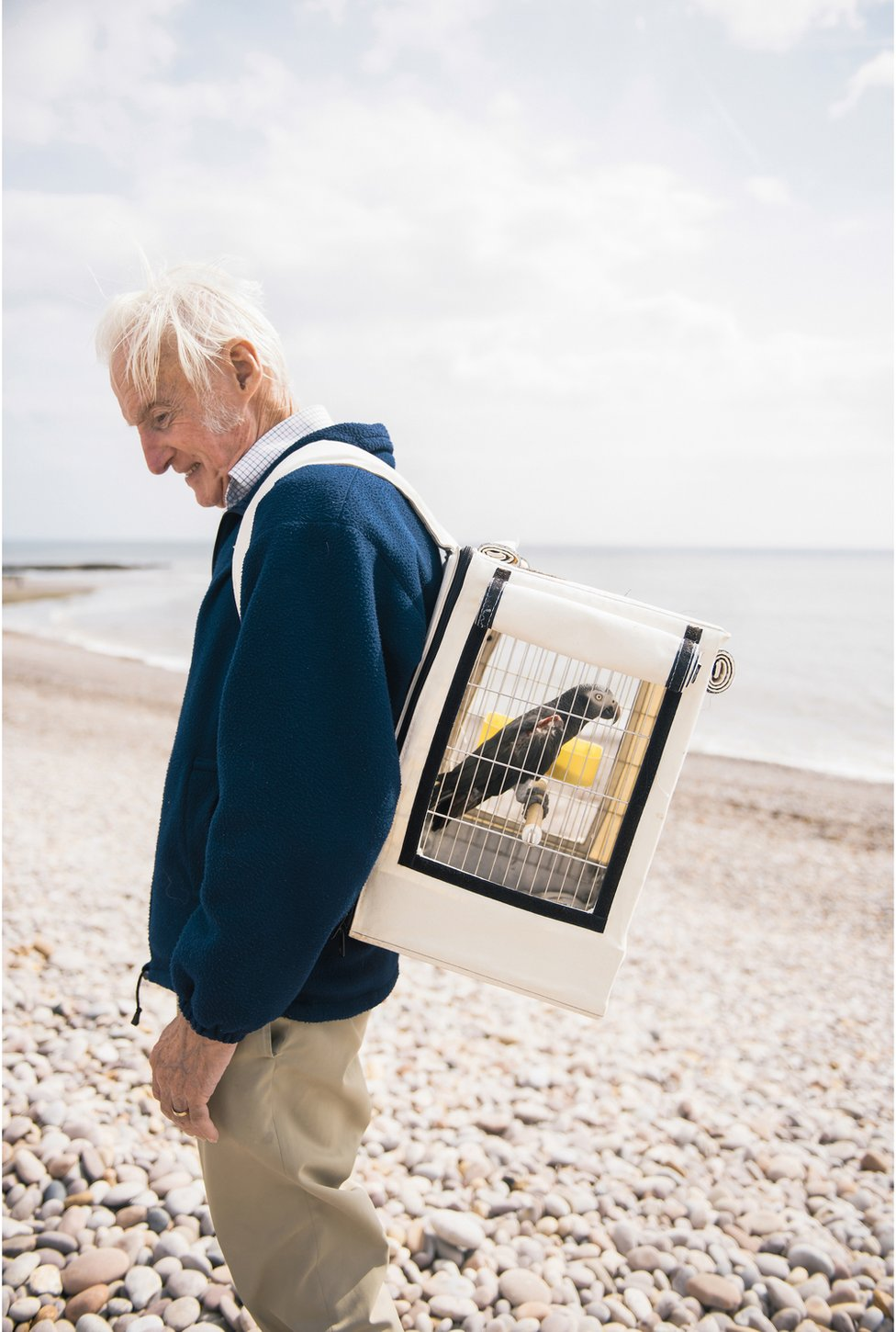 Portrait of Roy on the beach with an Africa grey parrot in a cage on his back