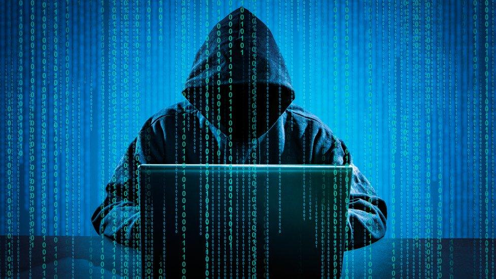 man in hoodie at laptop