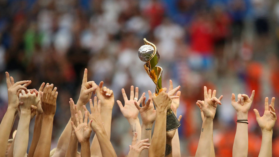 Hands of US team holding World Cup trophy
