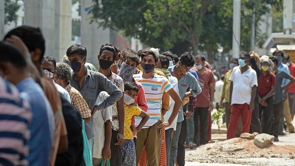 Fila de pessoas usando máscara na Índia