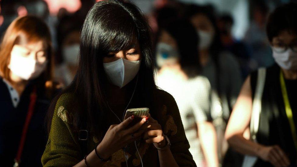 Jóvenes tailandesas con mascarillas protectoras