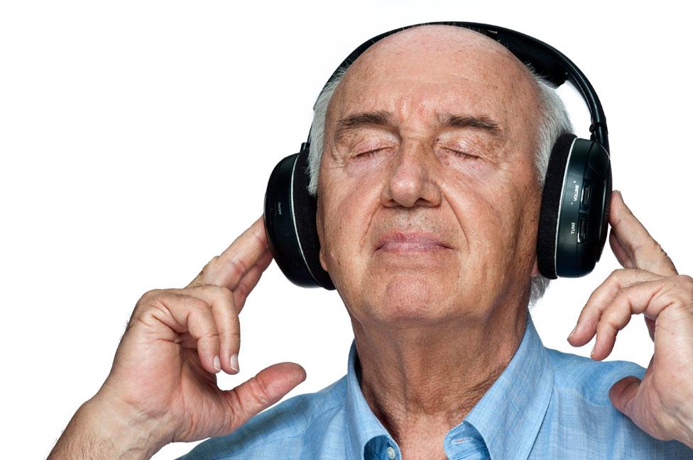 Un hombre semicalvo escucha música