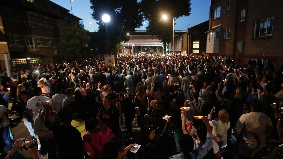 People hold candles outside Latymer Church, close to Grenfell Tower