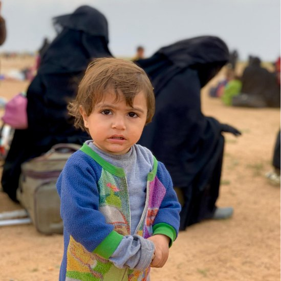 Un niño y varias mujeres en un campo de refugiados en Siria