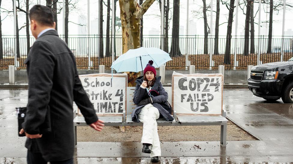 """Alexandria Villaseñor sentada frente a la ONU con un cartel que dice """"School strike 4 climate"""" o """"Huelga estudiantil por el clima""""."""