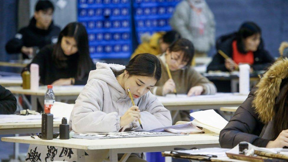 Mujer china escribiendo sobre un cuaderno