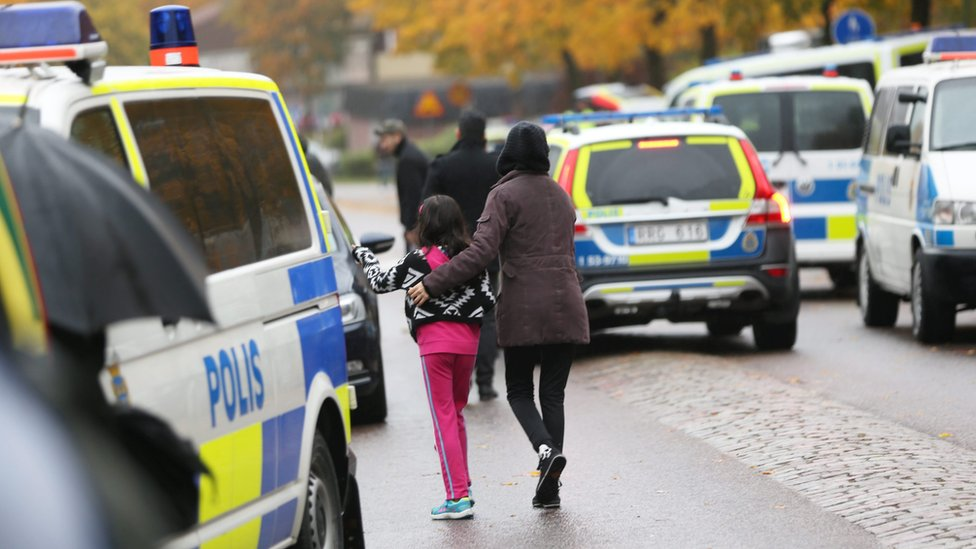 Students and parents leaving the school after a masked man attacked people with a sword at the Kronan school in Trollhaettan in western Sweden 22 October 2015.