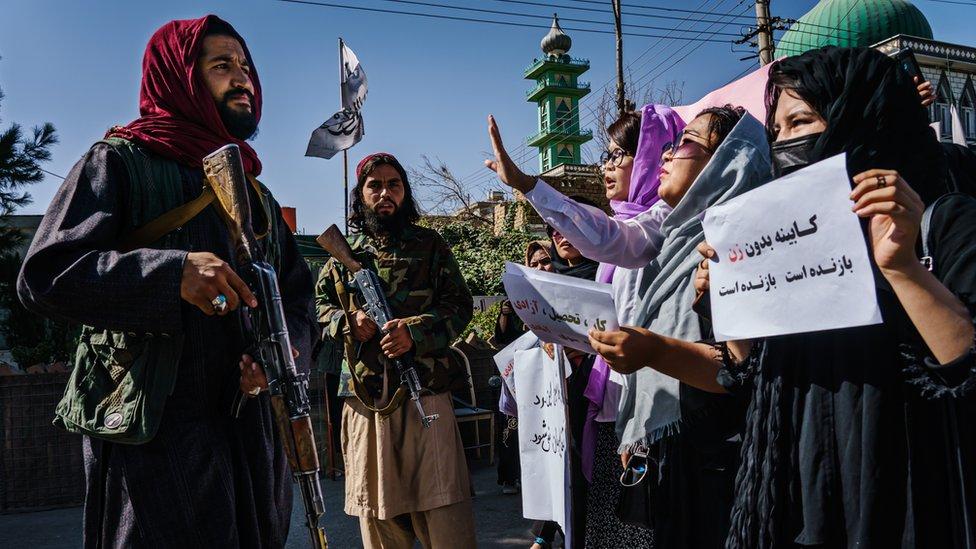 Taliban savaşçıları kadın eylemcilerin yanında