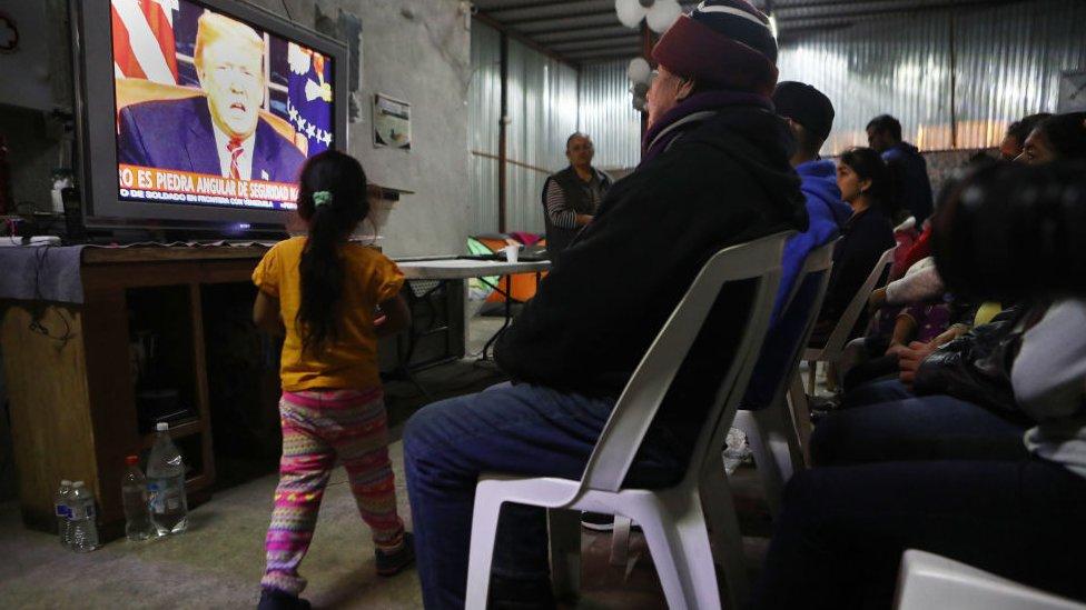 Un grupo de migrantes ven una transmisión televisiva donde aparece Trump en 2019.