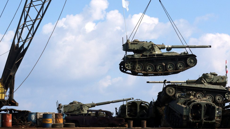 Workers unload old army tanks into the Mediterranean sea off the coast of Sidon, Lebanon, 28 July 2018.