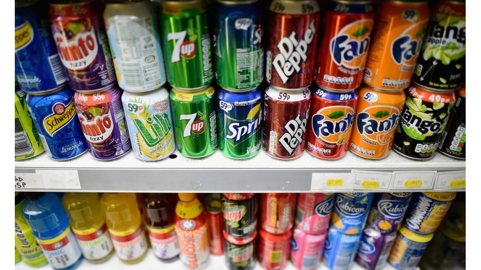 Fizzy drinks cans on a shelf