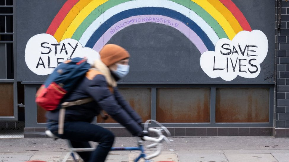 Uma pessoa passa de bicicleta por um mural de Covid no inverno do ano passado