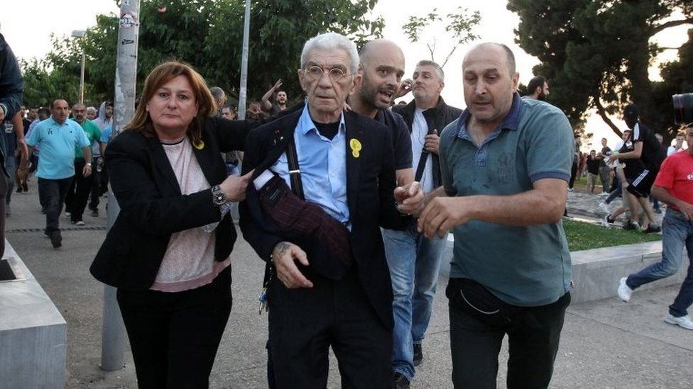 Mayor of Thessaloniki, Yiannis Boutaris (C), is aided after being attacked by a group of nationalists during Remembrance Day on 19 May 2018.