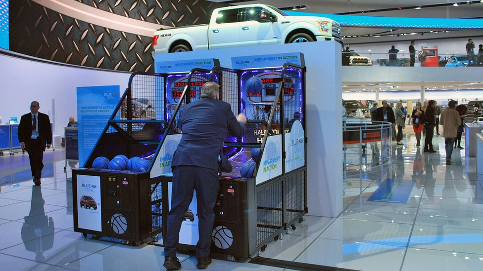 Man playing a basketball arcade game at the Ford stand at the Detroit motor show