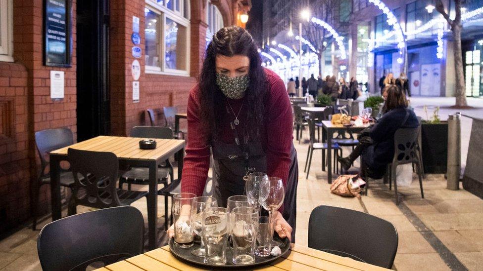 امرأة تحمل الأكواب في حانة في كارديف، ويلز