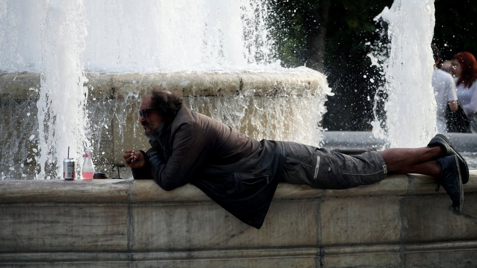 A man rests by the water fountain in Syntagma square in Athens, Greece, May 11, 2017