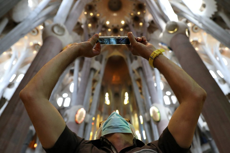 A man uses his phone as health workers, police officers and NGO staff members with their families visit the Sagrada Familia basilica as it reopens following the coronavirus disease (COVID-19) outbreak, in Barcelona, Spain, July 4, 2020