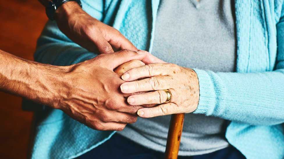 Close up of male holding hands of senior woman, - stock photo