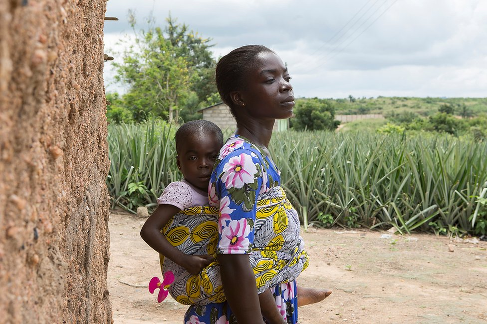 Christy Ansah carries her youngest daughter next to a farm