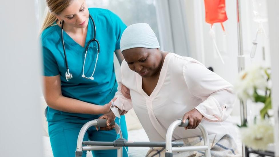 Profissional de saúde ajuda paciente a se movimentar