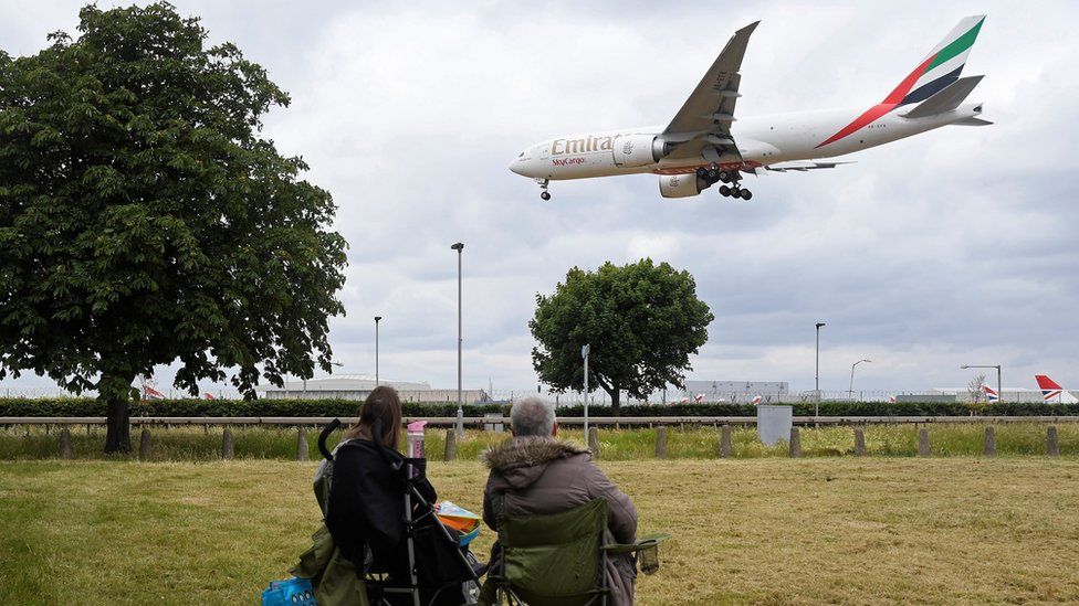 شخصان يشاهدان هبوط طائرة تابعة لشركة طيران الإمارات