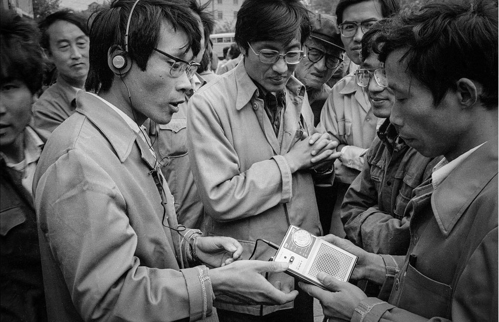 A man shows off a personal cassette player in the street