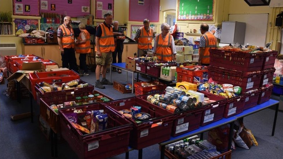 Volunteers with food to give to returning residents